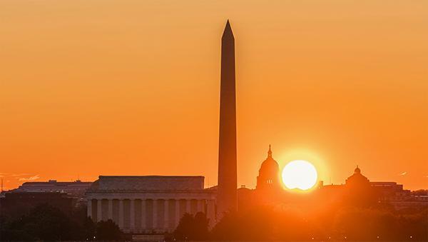 The sun sets over the Washington Memorial in Washington, D.C.